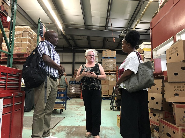 From left: Emmanuel Kimaro, Catherine Walker of the Kingman Area Food Bank, and Joyce Kimaro. Walker gave the Kimaros a detailed tour through the warehouse and facility while the Kimaros were visiting Tuesday. (Photo by Claire Whitley/Daily Miner)