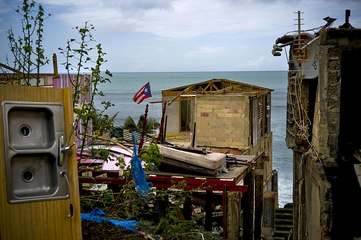 FILE - In this Oct. 5, 2017 file photo, a Puerto Rican national flag is mounted on debris of a damaged home in the aftermath of Hurricane Maria in the seaside slum La Perla, San Juan, Puerto Rico. An independent investigation ordered by Puerto Rico's government estimates that nearly 3,000 people died as a result of Hurricane Maria. The findings issued Tuesday, Aug. 28, 2018, by the Milken Institute School of Public Health at George Washington University contrast sharply with the official death toll of 64. (Ramon Espinosa/AP)