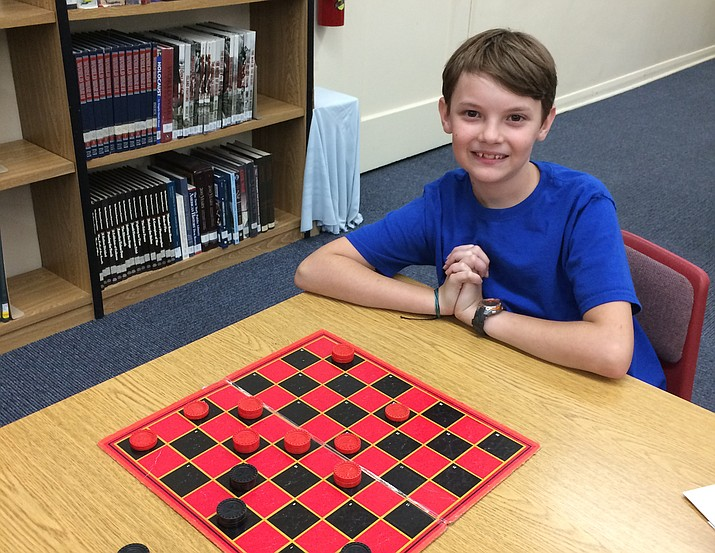 Mile High Middle School seventh-grader Bruce Reynolds plays checkers while attending a school program on the importance of attendance to academic achievement. He pledged to be an attendance ambassador with his peers because he sees its importance to his academic future. (Nanci Hutson/Daily Courier)