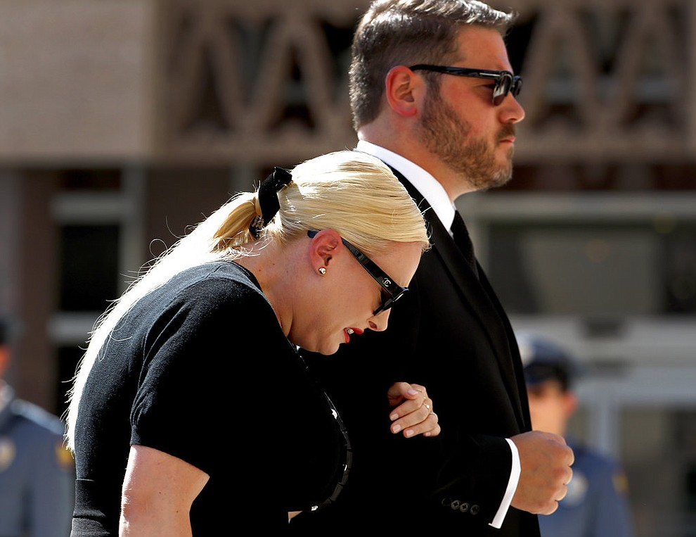 Meghan McCain cries as she and her husband Ben Domenech follow behind the casket carrying her father Sen. John McCain, R-Ariz., as they arrive for a memorial service, Wednesday, Aug. 29, 2018, at the Capitol in Phoenix. . (AP Photo/Matt York)