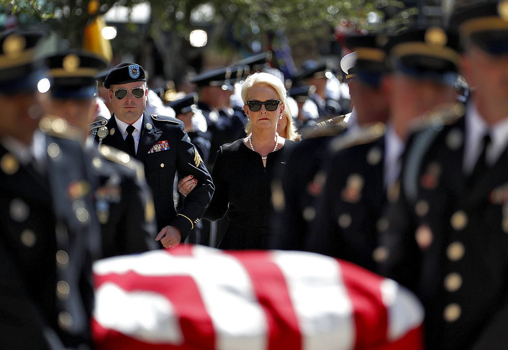 Cindy McCain escorted by her son, Jimmy McCain, left, follow behind military personal carrying the casket of Sen. John McCain, R-Ariz., into the Capitol rotunda for a memorial service, Wednesday, Aug. 29, 2018, at the Capitol in Phoenix.  (AP Photo/Matt York)