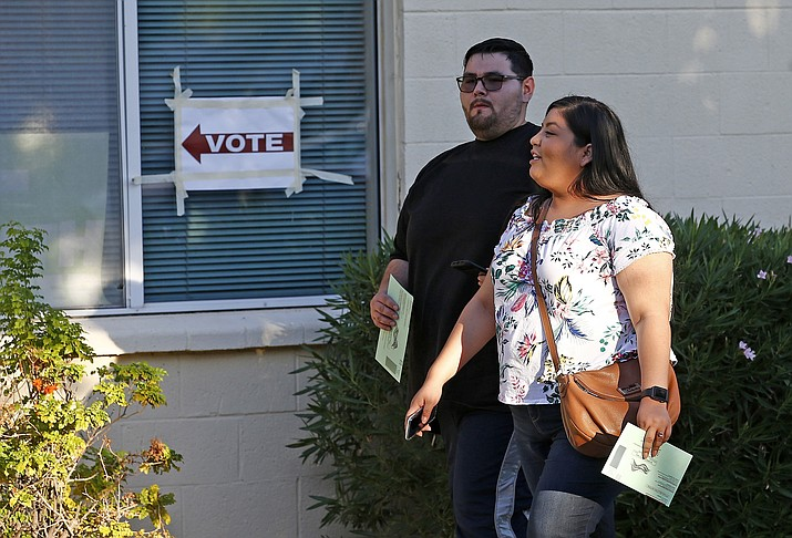 Voters arrive at a polling station with their ballots ready to be turned in on primary election day Aug. 28, in Phoenix. (AP Photo/Ross D. Franklin)