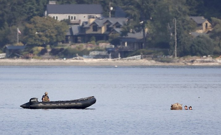 "A pair of U.S. Navy divers attach a rope to a ""reported unexploded ordnance"" drifting in the water between Brownsville Marina and Bainbridge Island, off Brownsville, Wash., Tuesday, Aug. 28, 2018. Brownsville is located a few miles south of Naval Base Kitsap - Keyport's torpedo testing range. The Navy was not immediately able to respond to a request for information. (Meegan M. Reid/Kitsap Sun via AP)"