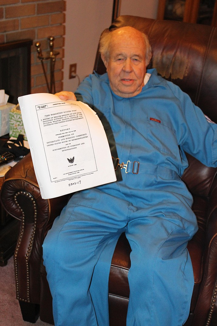 "Eddie Pattillo, one of the surviving Mohave County Downwinders, shows a report, ""The Forgotten Guinea Pigs,"" issued in 1980 about the recognized effects of low-level radiation exposure from nuclear testing in Nevada. (Photo by Hubble Ray Smith/Daily Miner)"