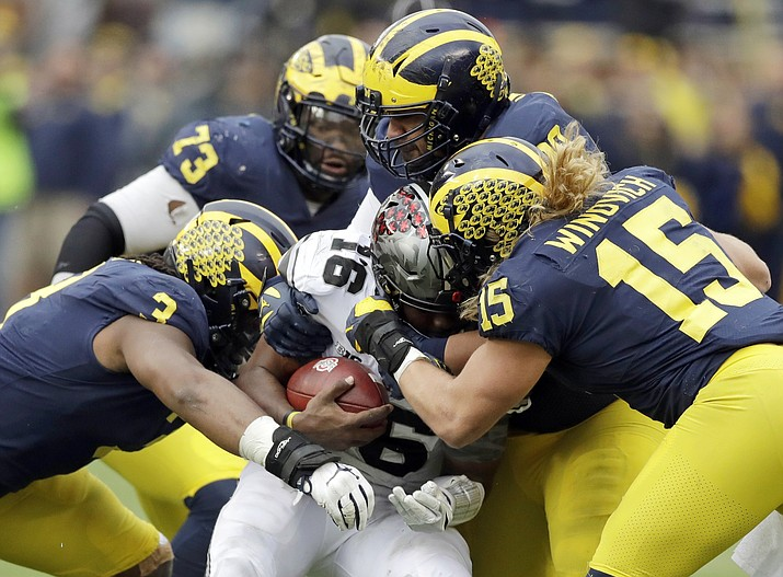 Ohio State quarterback J.T. Barrett (16) is sacked by Michigan defensive linemen Rashan Gary (3) and Chase Winovich (15) during the second half of their game Nov. 25, 2017, in Ann Arbor, Mich. When No. 12 Notre Dame has the ball Saturday night, No. 14 Michigan may have the advantage. The Wolverines appear to be loaded on defense with NFL-caliber players up front, at linebacker and in the secondary. (AP Photo/Carlos Osorio, File)