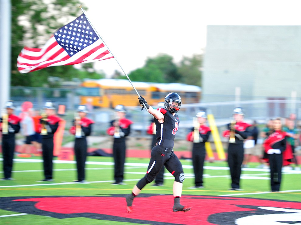 Bradshaw Mountain's Connor Scott (8) brings out the American Flag as the Bears take on the Youngker Roughriders in their home opener Friday, August 31, 2018 in Prescott Valley. (Les Stukenberg/Courier)