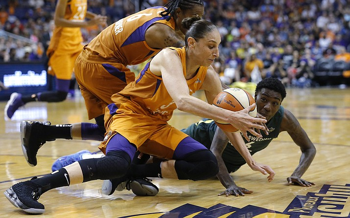 Phoenix Mercury guard Diana Taurasi, front, grabs a a loose ball next to Seattle Storm forward Natasha Howard, right, while Mercury guard Yvonne Turner (6) closes in during the first half of Game 3 of a WNBA basketball playoffs semifinal Friday, Aug. 31, 2018, in Phoenix. (Ross D. Franklin/AP)