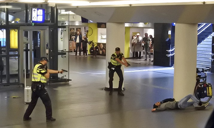 Dutch police officers point their guns at a wounded 19-year-old man who was shot by police after stabbing two people in the central railway station in Amsterdam, the Netherlands, Friday, Aug. 31, 2018. Police investigators in Amsterdam included an extremist attack as a possible motive for the stabbings of two people at a busy railway station Friday as authorities in the Dutch capital reported that the suspect shot by police is an Afghan citizen. (AP Photo)