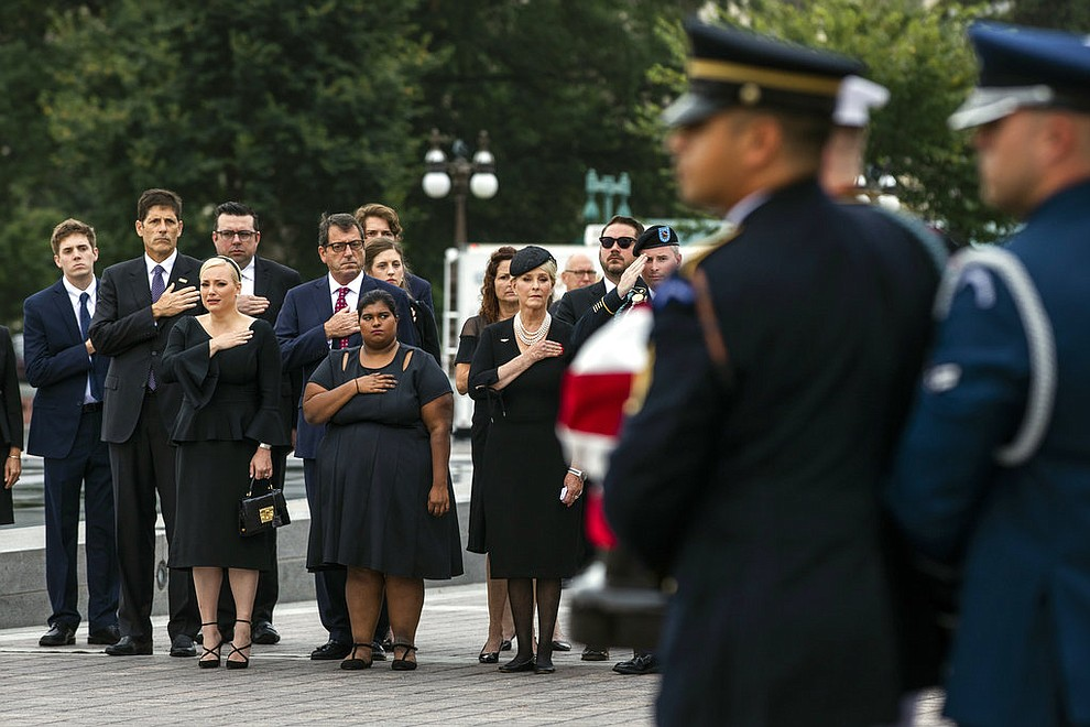 The family of Sen. John McCain, R-Ariz., front row from left, Meghan McCain, Bridget McCain and Cindy McCain, watches as his casket is carried to a hearse from the U.S. Capitol in Washington, Saturday, Sept. 1, 2018, in Washington, for a departure to the Washington National Cathedral for a memorial service. (Jim Lo Scalzo/Pool Photo via AP)