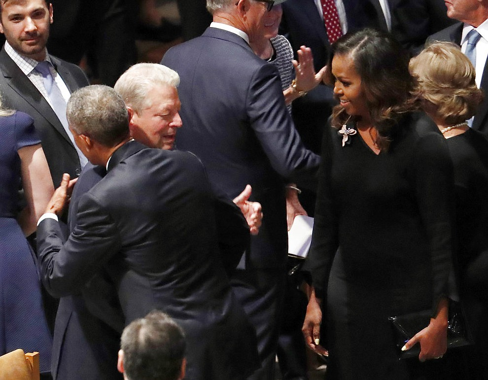 Former President Barack Obama hugs former vice president Al Gore as former first lady Michelle Obama watches before the memorial services for Sen. John McCain, R-Ariz., at Washington Nationals Cathedral in Washington, Saturday, Sept. 1, 2018. McCain died Aug. 25, from brain cancer at age 81. (AP Photo/Pablo Martinez Monsivais)