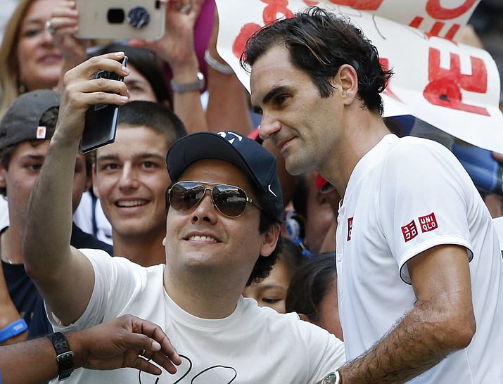 Roger Federer, of Switzerland, poses with a fan after defeating Nick Kyrgios, of Australia, during the third round of the U.S. Open tennis tournament, Saturday, Sept. 1, 2018, in New York. (Jason DeCrow/AP)