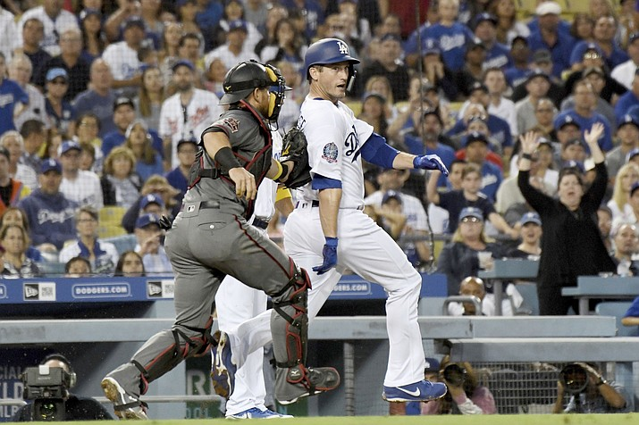 Los Angeles Dodgers' new acquisition David Freese is tagged out by Arizona Diamondbacks catcher Jeff Mathis during a rundown, after Freese was caught off third base on a grounder by Austin Barnes in the fourth inning of a baseball game, Saturday, Sept. 1, 2018, in Los Angeles. (Michael Owen Baker/AP)