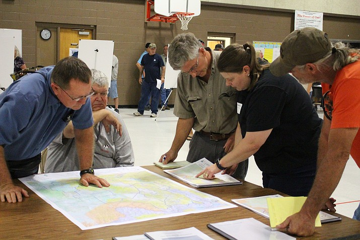 Amanda Dodson, second from right, manager of the BLM field office in Kingman, shows a map of trails to the folks attending Aug. 21 open house at Hualapai Elementary School. (Daily Miner file photo)