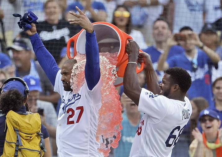 Los Angeles Dodgers' Matt Kemp, left, is doused by teammate Yasiel Puig after Kemp's two-run walk-off double against the Arizona Diamondbacks during a baseball game Sunday, Sept. 2, 2018, in Los Angeles. Los Angeles won 3-2. (Marcio Jose Sanchez/AP)