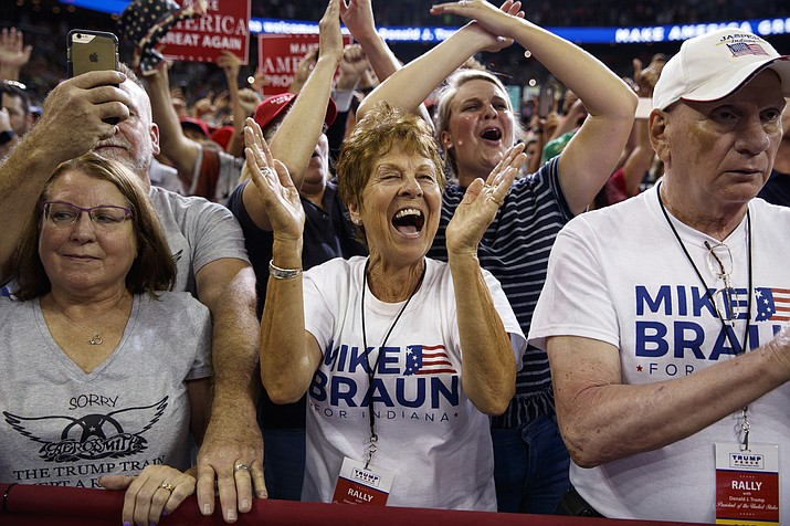 Supporters of President Donald Trump, wearing Mike Braun for Congress shirts, cheer as he arrives for a campaign rally Aug. 30, 2018, at the Ford Center in Evansville, Ind. Heading into the midterms, 2018's most volatile candidate is not on the ballot. But Trump is still taking his freewheeling political stylings on the road on behalf of his fellow Republicans, preparing to ramp up his campaign schedule in a campaign sprint to Nov. 6 (AP Photo/Evan Vucci/AP Photo)