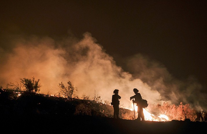 Firefighters keep watch the Holy Fire burning Aug. 9, 2018, in the Cleveland National Forest in Lake Elsinore, Calif. Researchers have expanded a health-monitoring study of wildland firefighters after a previous study found season-long health declines and deteriorating reaction times. (Ringo H.W. Chiu/AP Photos File)