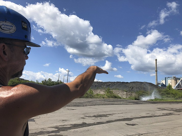 Brian Weekly, a contractor at West Virginia's Grant Town coal-fired power plant, gestures toward the small facility's smokestack, Thursday, Aug. 23, 2018 in Grant Town, W.Va. Weekly says opponents of the coal industry are behind warnings of health risks from smokestack emissions under the Trump administration's plan. (Ellen Knickmeyer/AP)