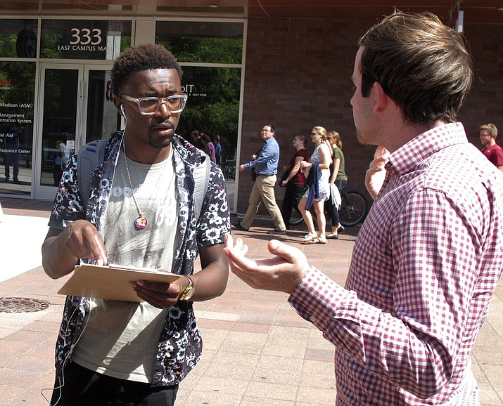 In this Thursday, Aug. 30, 2018 photo, University of Wisconsin freshman Kellen Sharp, left, gets information about registering to vote from NextGen America worker Sean Manning. Sharp says he's excited to vote. He and others at the Madison event think young people are more energized than ever. (Scott Bauer/AP)