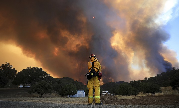 In this Aug. 2, 2018, file photo, a tower of smoke pours from Cow Mountain as Burney, Calif., firefighter Bob May keeps a watch on surrounding vegetation for spot fires during the River wildfire near Lakeport, Calif. Wildfires that have long shaped the landscape of the U.S. West are getting bigger and burning longer – bringing more choking smoke, deadly mudslides and habitat loss. (Kent Porter/The Press Democrat via AP, File)