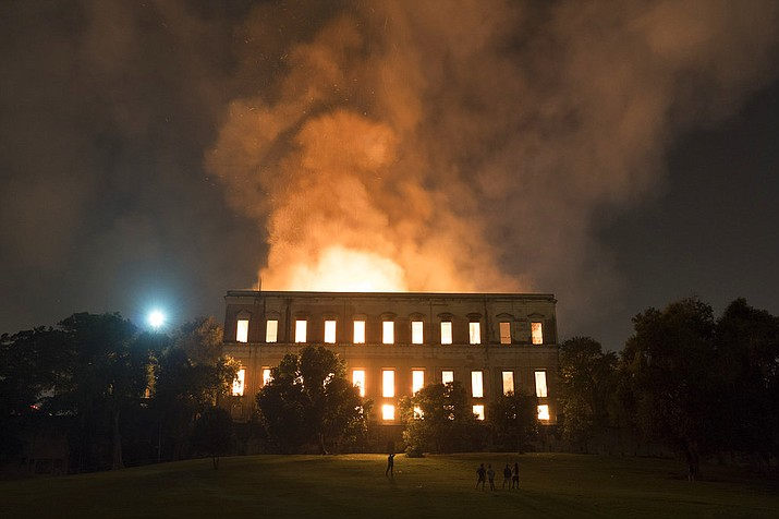 People watch as flames engulf the 200-year-old National Museum of Brazil, in Rio de Janeiro, Sunday, Sept. 2, 2018. According to its website, the museum has thousands of items related to the history of Brazil and other countries. The museum is part of the Federal University of Rio de Janeiro. (AP Photo/Leo Correa)