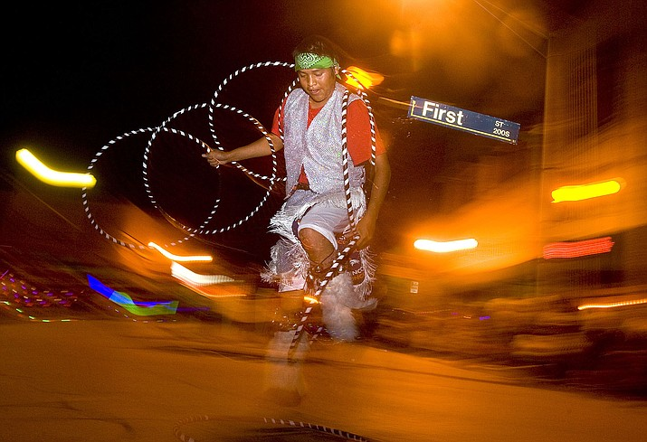 A 2010 file photo shows a hoop dancer wowing a crowd in downtown Gallup as part of the Gallup Inter-Tribal Indian Ceremonial night parade. Gallup surrounded by Navajo culture and Native arts and crafts is experiencing a tourism boom not seen since the 1970s. (Aaron Gardner/The Gallup Independent via AP)