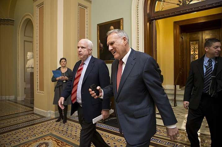 In this file photo, Sen. John McCain, R-Ariz., left, and Senate Minority Whip Jon Kyl, R-Ariz., leave the chamber at the Capitol in Washington, Sunday, Dec. 30, 2012. Sen. McCain's widow on Tuesday, Sept. 4, 2018, said Kyl will fill her late husband's seat. (AP Photo/J. Scott Applewhite)