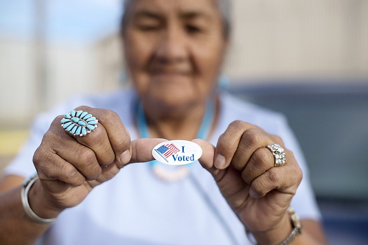 "Mildred James of Sanders, Arizona, shows her ""I Voted"" sticker as she waits for results of the Navajo Nation presidential primary election Aug. 28 in Window Rock. (AP Photo/Cayla Nimmo)"