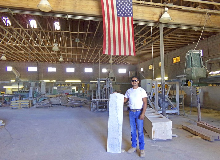 Stoneworld Plant Manager, CEO and R&J Crafts owner Juan Carranza stands next to one of 500 headstone cut from marble for the U.S. military. (Photo/Fayrene Hume)