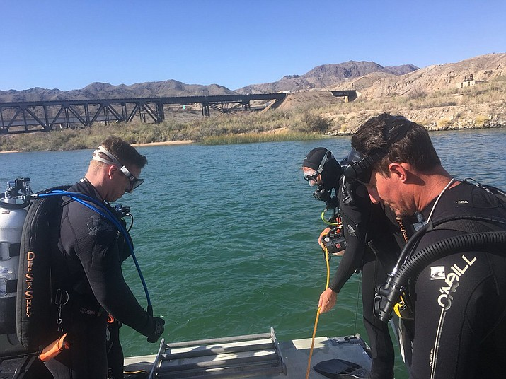 Los Angeles Sheriff Department Special Enforcement Bureau dive team members assist San Bernardino County Sheriff's officials in the search for three missing persons in the Colorado river Monday, Sept. 3, 2018, north of Lake Havasu, near Topock, Ariz. (Los Angeles Sheriff Department Special Enforcement Bureau via AP)