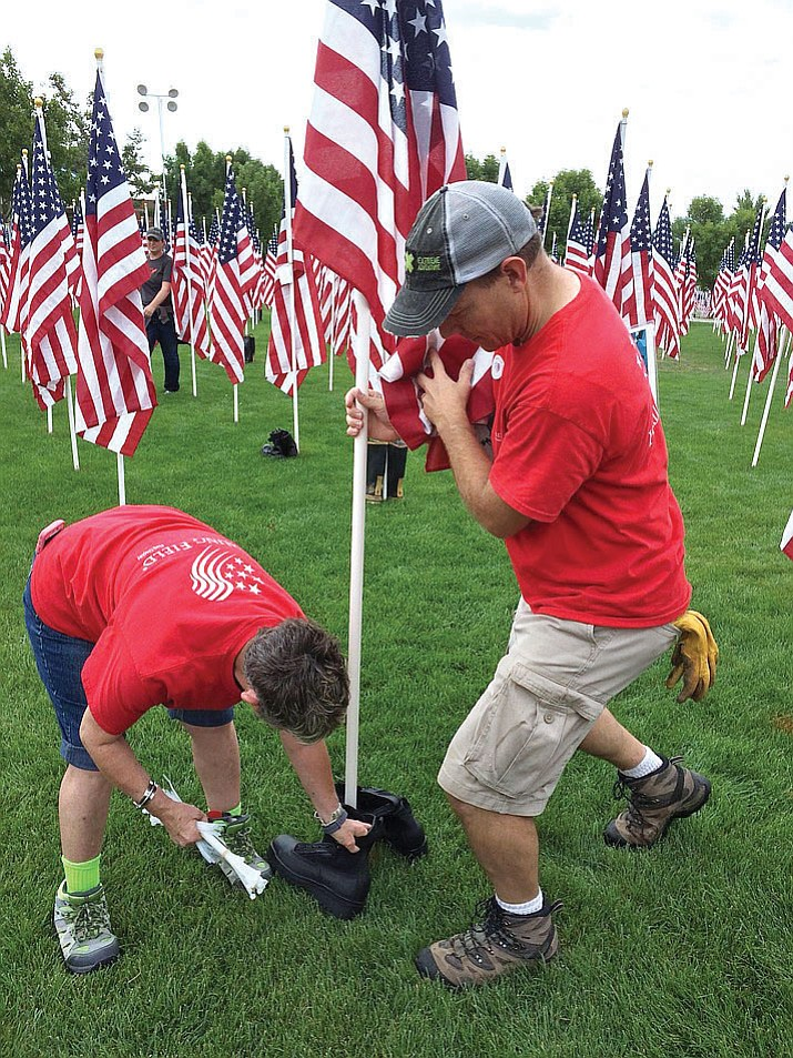 In this 2017 photo, Darlene Packard, Healing Field event coordinator, left, and Ryan Judy, assistant town manager for Prescott Valley, place a pair of police boots with the flag honoring Nathaniel Webb, 56, who died in the World Trade Center attack Sept. 11, 2001. The Healing Field at the Prescott Valley Civic Center, with 3,019 flags, is open to the public 24/7 from Sept. 7 to Sept. 14. (Sue Tone/Tribune, file)