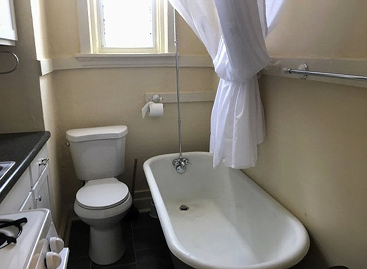 This photo from a rental ad provided by S.F. Shannon Real Estate Management LLC shows a toilet and bathtub in the kitchen of a 200-square-foot apartment in St. Louis. The toilet, bathtub, oven and sink all share a room. A St. Louis man is the new tenant of the tiny apartment. (S.F. Shannon Real Estate Management LLC via AP)
