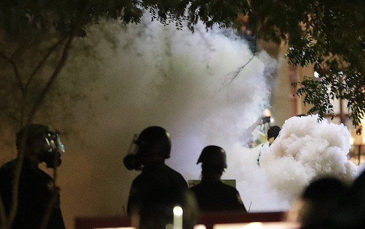 Smoke billows after police used tear gas on protesters Aug. 22, 2017, outside a rally held by President Donald Trump in downtown Phoenix. Two advocacy groups filed an excessive-force lawsuit on Tuesday, Sept. 4, 2018, against the Phoenix Police Department over the conduct of officers during a protest outside the rally. The suit alleges officers deliberately targeted anti-Trump protesters and showed a preference toward Trump supporters. The police department declined to comment on the lawsuit. (Matt York, AP Photo File)