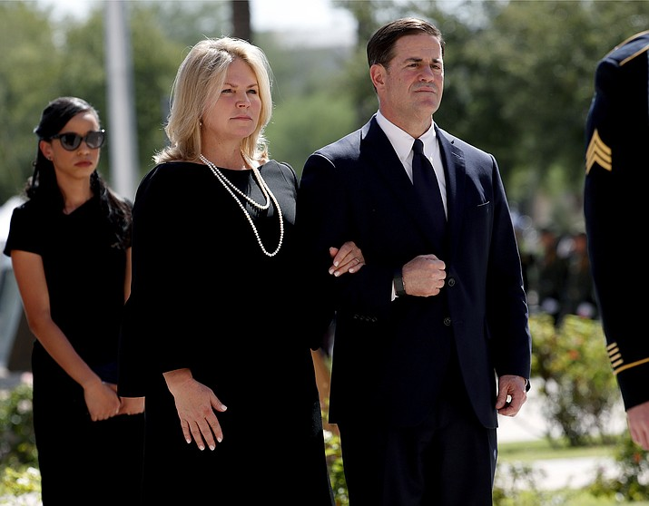 In this Aug. 29, 2018 file photo, Gov. Doug Ducey and his wife, Angela Ducey, follow the casket of Sen. John McCain, R-Ariz., into a memorial service at the Capitol in Phoenix. Arizona has developed a reputation over the past decade for being one of the country's greatest political flashpoints. Ducey has navigated the state's political waters with a buttoned-down approach. (Matt York/AP, File)