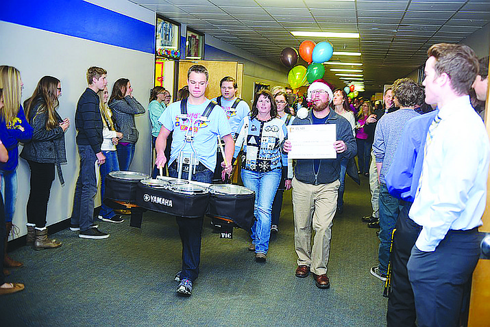 Prescott Unified School District Superintendent Joe Howard leads a drumline and members of the Prescott Education Foundation through Prescott High School as they went around on Friday, December 9 to district schools and handed out checks to teachers who had applied and received grants for special projects. (Les Stukenberg/The Daily Courier, file)