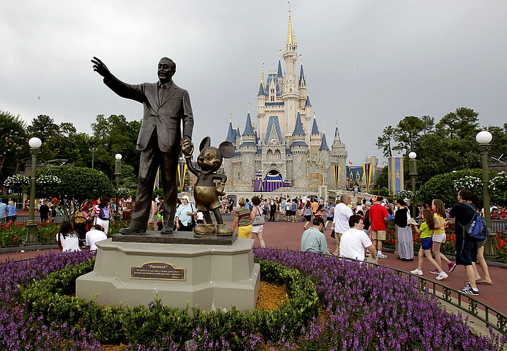 Visitors stroll along Main Street at Walt Disney World in Lake Buena Vista, Fla., on June 5, 2012. Thousands of Walt Disney World workers are voting on whether to accept a contract proposal that would increase the starting minimum wage to $15 an hour over the next three years while enabling Disney to use more part-time workers and require new workers to stay in their positions longer before transferring. (AP Photo/John Raoux, AP Photo File)