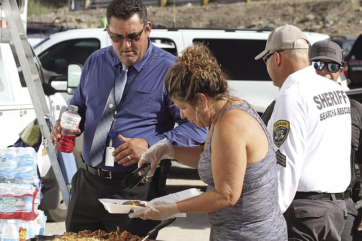 Burgers by the Bridge owner Harriet McLearen serves a meal prepared by Lin's Little China to Mohave County Sheriff Doug Schuster Tuesday afternoon at Topock 66. (Photo by Brandon Messick/ Today's News-Herald)