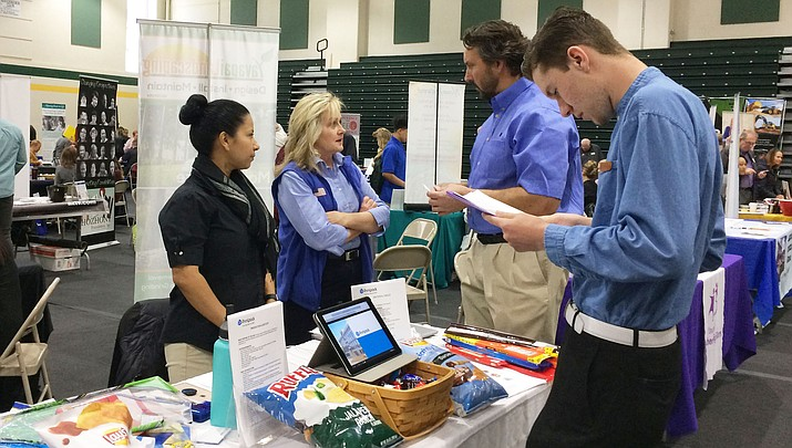 In this March 2018 file photo, Vinson White, right, of Dewey-Humboldt, looks over material at a job and career fair hosted by Yavapai College. The college's Regional Economic Development Center (REDC) one of the sponsors of the Prescott Valley Job Fair taking place from 4:30 to 7 p .m. Wednesday, Sept. 12, at the Prescott Valley Events Center. (Sue Tone/Courier File)