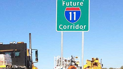 Workers are shown putting up a sign identifying U.S. 93 as the Future I-11 Corridor. There are only 39 miles remaining between Wickenburg and the Nevada border north of Kingman that are not  four-lane divided highway miles. (ADOT file photo)