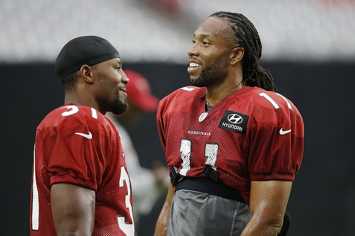 In this Aug. 2, 2018, file photo, Arizona Cardinals wide receiver Larry Fitzgerald (11) talks with running back David Johnson (31) during an NFL football practice, in Glendale, Ariz. The Washington Redskins will be trying to give coach Jay Gruden his first victory in a season opener in five tries when they face the Cardinals in Arizona on Sunday. Sept. 9, 2018. The team Gruden will face is something of a mystery, with a rebuilt offense and redesigned defense under new coach Steve Wilks. (Ross D. Franklin/AP, file)