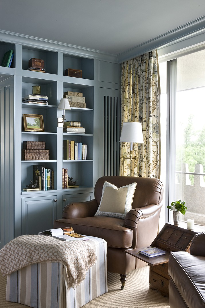 In this home library designed by Kelley Proxmire in Washington, D.C., an ottoman helps turn a comfortable chair into the perfect place for reading. (Angie Seckinger/Sherry Moeller via AP)