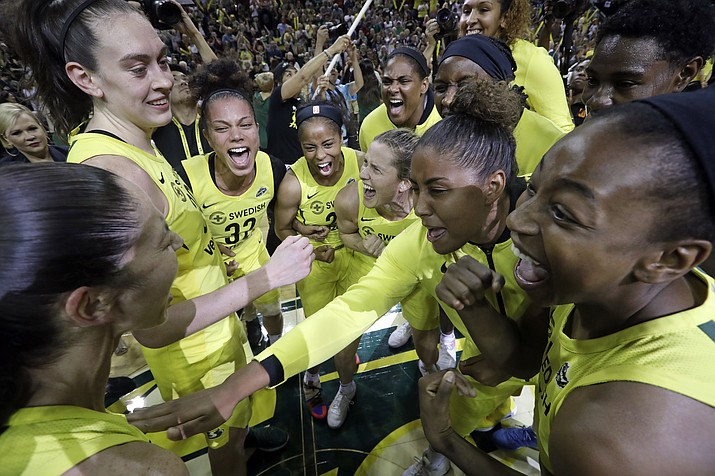 Seattle Storm players gather in a celebratory huddle after a 94-84 win over the Phoenix Mercury during Game 5 of a WNBA basketball playoff semifinal, Tuesday, Sept. 4, 2018, in Seattle. The Storm advanced to the WNBA finals. (Elaine Thompson/AP)