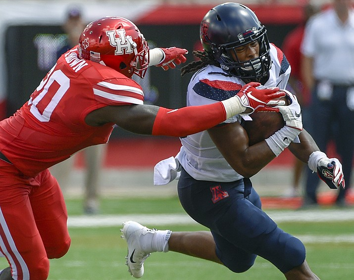 Arizona running back Gary Brightwell, right, is tackled by Houston linebacker Roman Brown during the first half of an NCAA college football game, Saturday, Sept. 8, 2018, in Houston. (Eric Christian Smith/AP)
