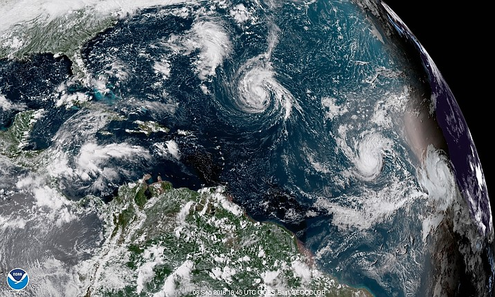 This enhanced satellite image shows Tropical Storm Florence, center, in the Atlantic Ocean on Saturday, Sept. 8, 2018 at 2:45 p.m. EDT. (NOAA via AP)