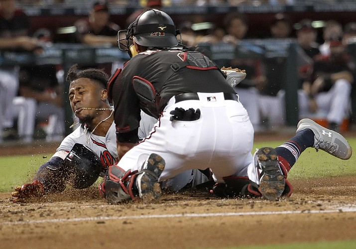 Atlanta Braves' Ozzie Albies is tagged out by Arizona Diamondbacks' Jeff Mathis (2) as he tries to score on a fielders choice hit into by Dansby Swanson during the second inning of a baseball game, Saturday, Sept. 8, 2018, in Phoenix. (Matt York/AP)