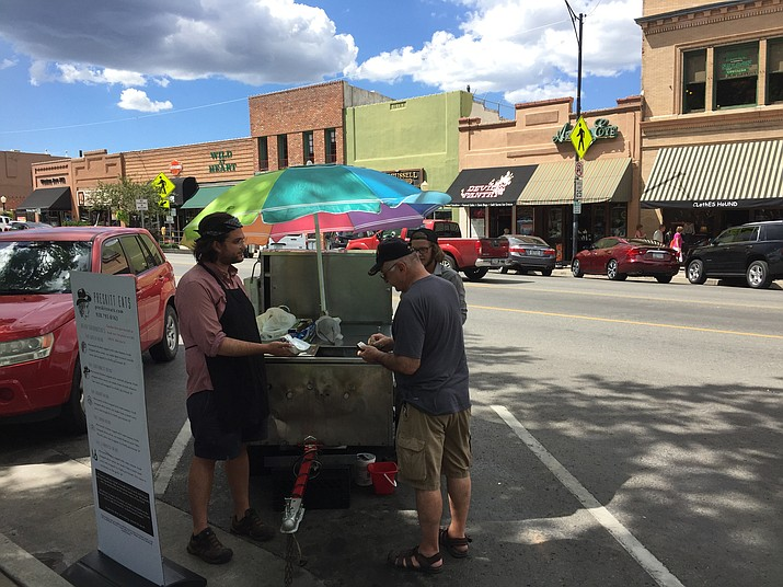 Vasili Markou, owner of Preskitt Eats, serves a customer this past week from his vendor cart alongside the courthouse plaza. (George Lurie/Courier)