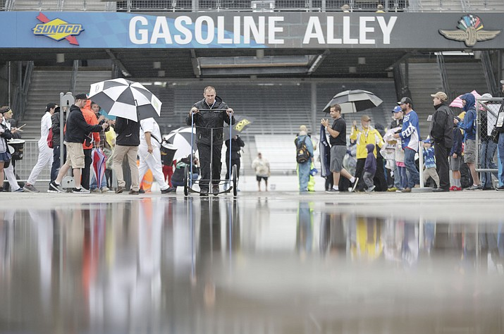 Fans and crew members walk through the rain soaked garage area as rain canceled track activity for the Brickyard 400 auto race at Indianapolis Motor Speedway, in Indianapolis Saturday, Sept. 8, 2018. (Michael Conroy/AP)