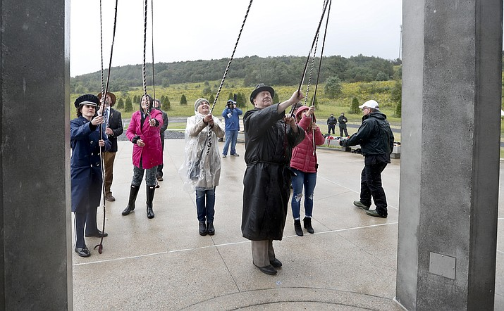 Members of passenger families, friends and volunteer repesentatives pull the ropes to ring the chimes at the dedication of the 93-foot tall Tower of Voices on Sunday, Sept. 9, 2018 at the Flight 93 National Memorial in Shanksville, Pa. The tower contains 40 wind chimes representing the 40 people that perished in the crash of Flight 93 in the terrorist attacks of Sept. 11, 2001.(Keith Srakocic, Pool, AP Photo)