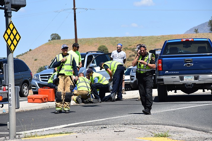 Emergency personnel treat an elderly man who was injured either during or soon after a four-vehicle collision at the intersection of Highway 69 and Fain Road in Dewey Monday afternoon, Sept. 10. (Richard Haddad/WNI)