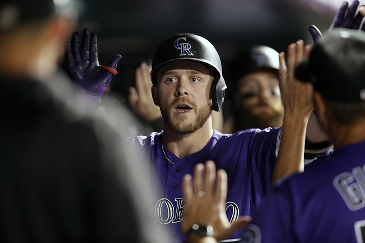 Teammates congratulate Colorado Rockies' Trevor Story as he returns to the dugout after hitting three-run home run off Arizona Diamondbacks relief pitcher Silvino Bracho in the fifth inning of a baseball game Monday, Sept. 10, 2018, in Denver. (David Zalubowski/AP Photo)