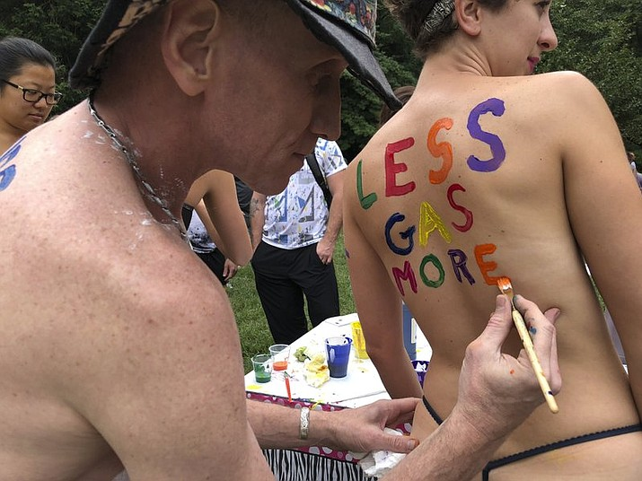 Bicyclist Olivia Neely gets a message advocating for less consumption of fossil fuels painted on her back at the Philly Naked Bike Ride in Philadelphia, Saturday, Sept. 8, 2018. (AP Photo/Dino Hazell)